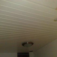 Kylpyhuoneremontin yhteydessä uusittiin myös kylpyhuoneen kattopanelointi. Materiaaliksi valittiin valkoinen mäntypaneeli. Asiakkaan toivomusten mukaisesti valaistuksen määrää lisättiin yhdestä valaisimesta kahteen.