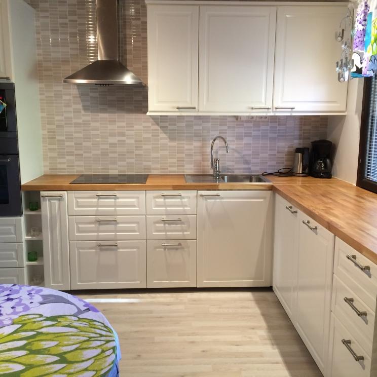 Omakotitalon keittiö rakennettiin pääosin Ikea-kalusteilla. Oman haasteensa projektiin toi ikkunan paikka. Jotta kaapit ja 4 cm:n paksuinen tammitaso saatiin sopimaan ikkunan alle, oli kohteeseen tilattava erikseen jalat, jotka ovat vain noin 6 cm:n korkuiset. Myös avohyllykkö rakennettiin kohteeseen mittatilaustyönä.