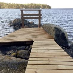 Laituri rakennettiin Näsijärven rantakivikkoon asiakkaan toiveiden mukaisesti. Samalla mahdollistettiin yhtenäinen kulku suoraan patiolta rantaan saakka.